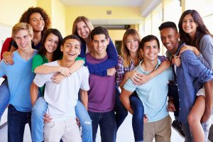 A group of multi-ethnic youth gathered in the community room, smiling and hugging for a photo after Connected Family Fun, LA outing.