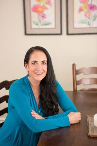 Smiling, Caucasian, female therapist in a blue top sitting at a wooden dining table promoting her options for Family Trauma Therapy in Client's Home ready for contact.