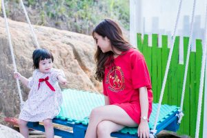 Contact Abby for Therapy for families with Asian toddler girl in dress with red bow sitting next to mom in red dress on outdoor swing with light blue cushion.