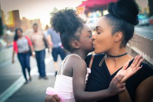 On a Post-Adoption Family Therapy field trip to the city, an African American adoptive mother holds young African American adopted daughter in a pink tutu while fondly kissing her on the cheek.