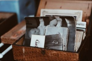 Old brown box of black and white photos, including baby various adult portraits reminisced about during Family Trauma Therapy to strengthen family connections.