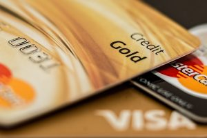 Three gold colored Visa and MasterCard credit cards laying on a black table, prompt questions regarding Family Therapy Rates-Insurance with Abby McCarrel.