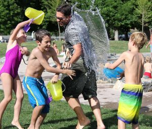 Caucasian family plays with colorful buckets throwing water on each other as the result of good work in Post-Adoption Family Therapy.