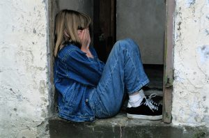 Family Therapy for young Caucasian girl dressed in blue jeans, jean jacket and sneakers, sitting, knees bent up, in doorway to outdoors with face in hands, crying and angry