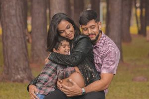 Loving, mixed race, Hispanic, African American family of a bare belly pregnant mother, father and son in a group hug in the woods benefit from Family Therapy Services.