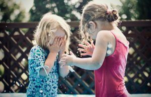 Behind a brown lattice fence, two young Caucasian girls, one wearing blue and one wearing pink, are in a water fight with younger child covering her face with both hands, crying needing Family Therapy services.