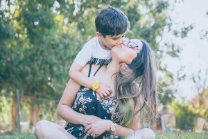 Mother figure with glasses and long brown, straight hair, sitting cross legged outdoors near trees, leaning back and getting a kiss from toddler boy. Contact Abby.