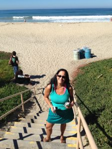 Caucasian woman with long dark hair and sunglasses standing on stairs leading down to the beach with sand and ocean in the background on a Connected Family Fun, LA outing.