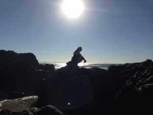 Silhouetted figure of a woman with long brown hair and sun glasses, squatting on rocks next to the ocean's edge having fun with her family on a Connected Family Fun, LA day at the beach.