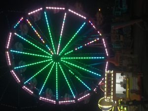 Ferris wheel at night lit up with green and purple lights on a Connected Family Fun, LA night out.