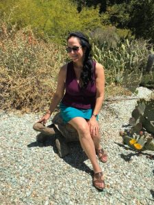 Woman with long, dark hair pulled to the side and sunglasses sits on a stone turtle sculpture in a rock garden surrounded by cacti with yellow flowers in Arlington Garden.