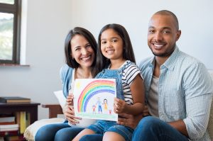 Smiling daughter showing painting of family with parents and beautiful rainbow during Family Therapy session, planning a Connected Family Fun, LA outing.