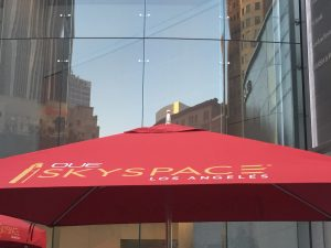 "Red umbrella with the writing ""OUE SKYSPACE"" against the mirrored downtown LA building at street level at dusk."