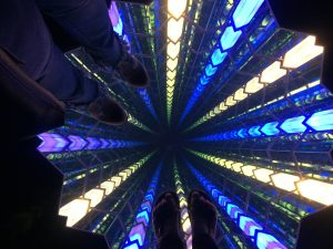 Pair of legs standing on mirror with multi-colored lights, giving the illusion that one can see all the way down 70 flights at OUE Skyslide, lA.