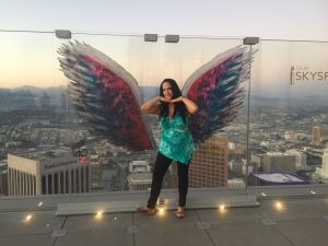 Caucasian women with long dark hair poses in front of angle wings painted on clear plastic wall on observation deck at OUE Skyslide, LA, overlooking the city at dusk.
