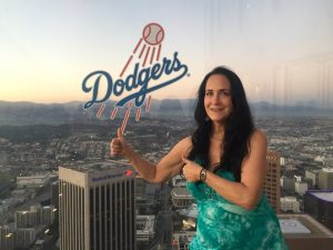 Caucasian female with long dark har poses with two thumbs up in front of Dodgers sign decal on clear plastic wall overlooking the city of LA and Dodger Stadium.