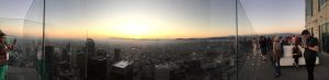 Panoramic view on top of the OUE Skyslide looking out over the city of LA at bright, yellow sun as it sets.
