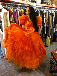 Woman in long dark hair pulled over to the side models orange floor-length, ruffled dress with big puffy sleeves inside vintage clothing store during a Connected Family Fun, LA: Topanga Canyon trip.