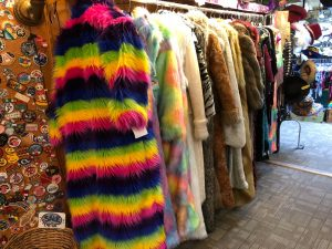 Inside a vintage boutique is a rack of extremely colorful coats on a shopping day on a Connected Family Fun, LA: Topanga Canyon activity.