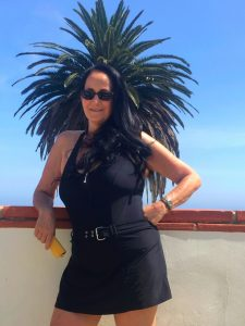 Woman with dark long hair in black one piece bathing suit leans with one arm on a wall with palm tree behind on a Connected Family Fun, LA; Malibu Lagoon outing.