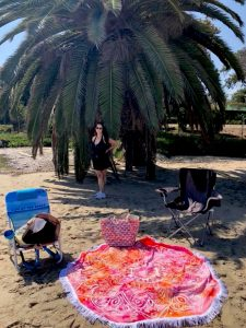 Caucasian woman in a black bathing suit with long dark hair stands under a large, wide palm tree on the beach with beach chair and towel on a homework assignment for Connected Family Fun, LA; Malibu Lagoon family activity.