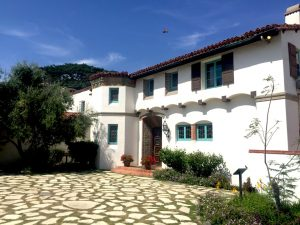 Spanish-style house with cobble stone courtyard, surrounded by green trees on a family counseling assignment from Connected Family Fun, LA; Malibu Lagoon.