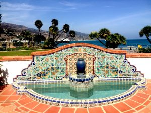 Colorful tile fountain with blue-green water on a patio with palm trees and beach in the background during a Connected Family Fun, LA; Malibu Lagoon day trip.
