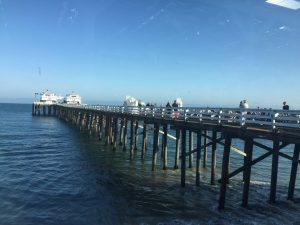 Long tall ocean pier with people walking and Malibu Farms Cafe at the end, a with building with a red roof on a Connected Family Fun, LA; Malibu Lagoon Family Counseling homework assignment.