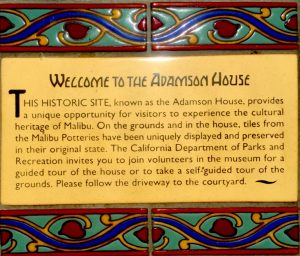 "Yellow tiled sign stating, ""Welcome to the Adamson House,"" with information about the history of the house with blue decorated tiles around the outside on a Connected Family Fun, LA; Malibu Lagoon beach day family therapy outing."