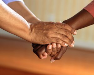 Two adults, one caucasian and one African American hold hands during a family therapy session.