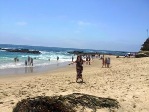 Young woman on a beach with other beach goers has her arms spread out mid-twirl, wearing sunglasses and holding her phone on a Connected Family Fun, LA; Aliso Beach, Laguna family therapy homework assignment.