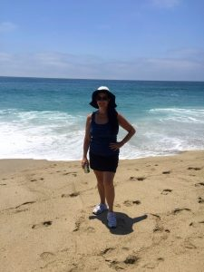 Woman in a white beach hat, long dark hair pulled to the side and sunglasses stands on the sandy beach with one hand on her hip and the other holding a soda, smiling with the deep blueish-green ocean in the background while spending time on a Connected Family Fun, LA; Aliso Beach, Laguna family therapy homework assignment.