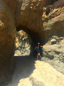 Woman in white baseball cap and long dark hair leans on rocks under a tunnel on the sandy beach on a bright sunny day.