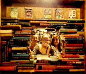 Three young caucasian women peek through a display of books, smiling and happy to be on an outing to the Last Bookstore as gifted children.