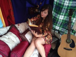 Teen girl relaxes in homemade tent, reading a book