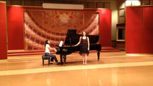 Young caucasian woman with short, curly bobbed brown hair, stands as a gifted child in front of a black grand piano in a large recital hall with red coloring and an accompanist.