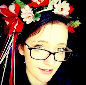 Young caucasian woman with dark hair, glasses and a flower crown, expresses herself as a gifted child.
