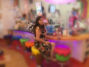 Connected Family Fun, LA; Aliso Beach, Laguna accompanies a young woman as she sits at multi-colored ice cream bar.