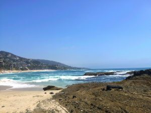 View from tide pool rocks across sandy beach with deep blue water looking at beach and cliff houses on a Connected Family Fun; LA Aliso Beach, Laguna family fun day.