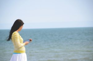 Mother walks along the beach with ocean in the background looking at phone getting online therapy for her stress with gifted children living in Arcadia, CA