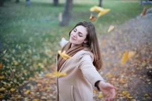 Caucasian young mother with brown hair and tan sweater twirls among falling yellow leaves, happy about finding herself working with SENG therapist.