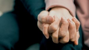 Therapist and parent of gifted student hold hands during depression and suicide therapy session in Arcadia, CA