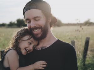 Father holding young daughter in his arms in a grass field in front of a fence