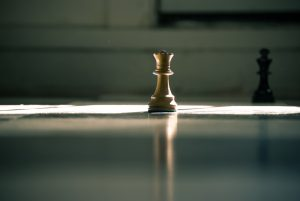 Single chess piece sits on table backlit by bright light.