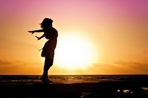 Silhouetted woman at sunset on the beach reaches her arms back and looks up at the orange and pink sky.