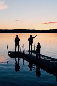 three-people-on-a-wooden-fishing-docks-