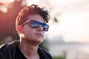 Caucasian, male teen with sunglasses and brown hair and sundown