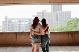 two-women-standing-inside-parking-lot-