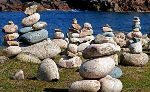 Numerous piles of stacked rocks dot the sand with blue water in the background helping with anxiety and stress.