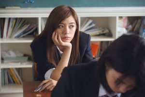 Young woman in school uniform leaning on her school desk anxious and stressed.